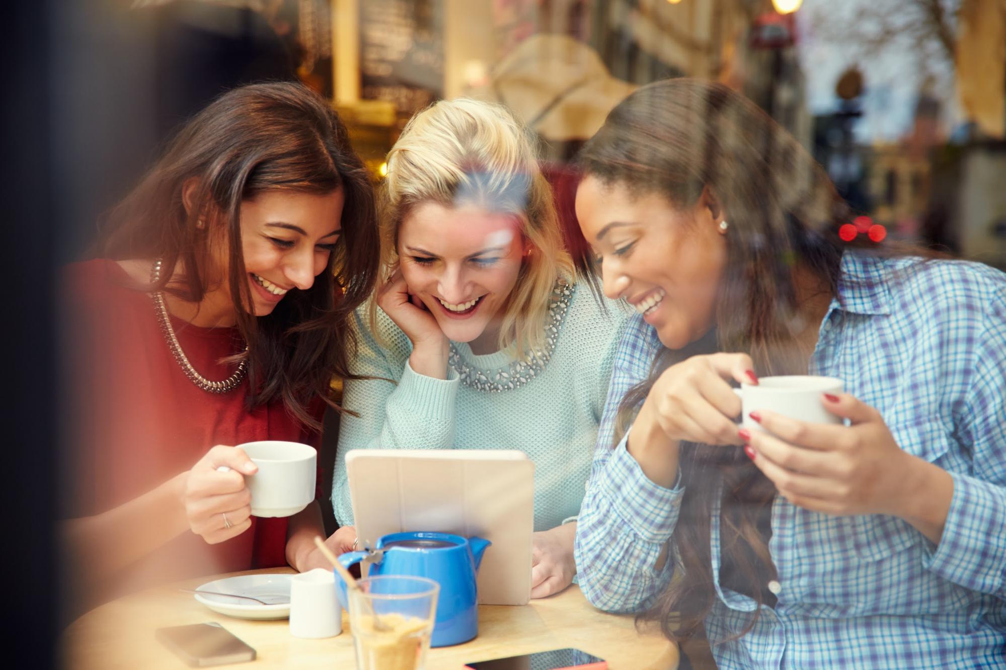 three women watching ipad